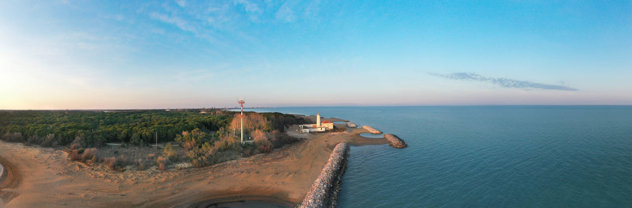Bibione lighthouse from above at sunset in a panoramic aerial viewwith sea and blue sky