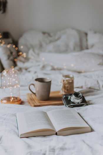 Coffee cup and book on bed at home