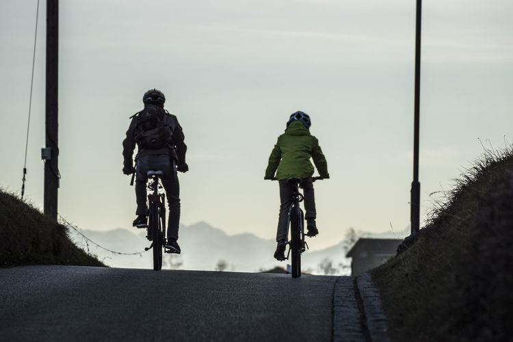 Rear view of men on bicycle in city