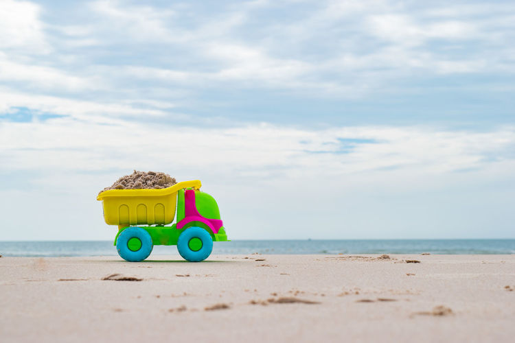 Toy toys on beach against sky
