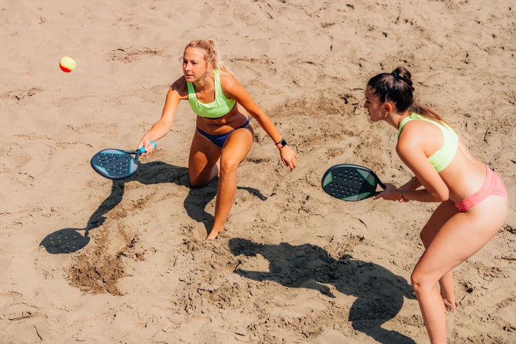Female team playing beach tennis