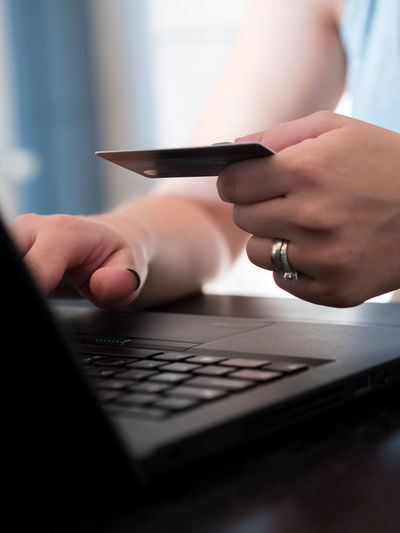 Woman paying online on internet with credit card Goods Home Woman Young Card Caucasian Close-up Credit Card Debit Holding Human Hand Indoors  Internet Laptop Notebook Online  Pay Paying Purchase Purchases Remote Technology