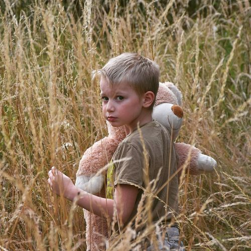 Portrait of boy with teddy bear standing on field