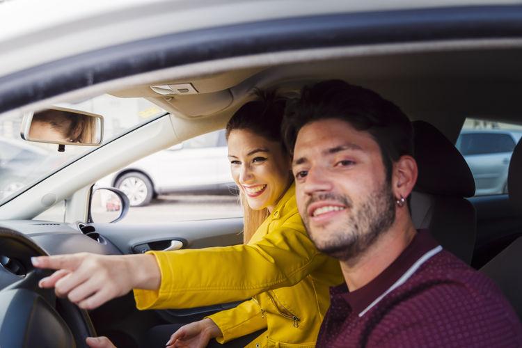 Portrait of happy friends sitting in car