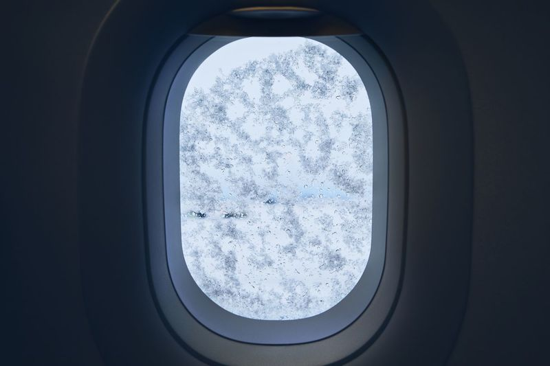 Snowing at the airport. View from window of the airplane covered by snow before deicing. Window Snow Air Vehicle Airplane Nature Winter Mode Of Transportation Day No People Transportation Vehicle Interior Cold Temperature Indoors  Snowing Snowflake Covered Winter Wintertime Frost Ice Travel Transportation Weather Deicing Airport