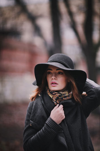 Attractive, charming young woman in a hat and dark coat walking in the autumn park.