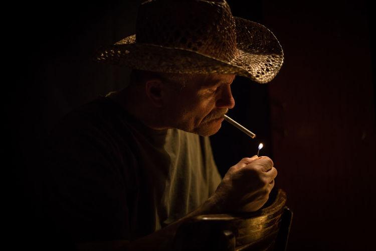 Senior man smoking cigarette in darkroom