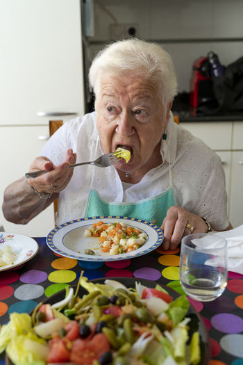 Mid adult man eating food at home