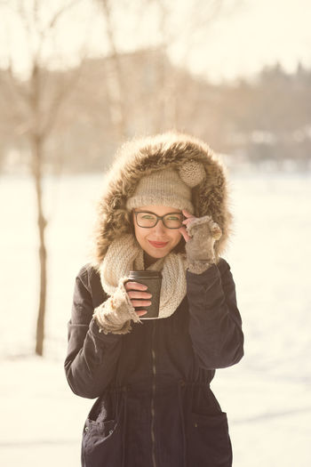 Cold Temperature Communication Day Eyeglasses  Focus On Foreground Front View Fur Coat Holding Leisure Activity Lifestyles Mobile Phone Nature One Person Outdoors Portable Information Device Real People Smiling Snow Standing Technology Warm Clothing Winter Wireless Technology Young Adult Young Women
