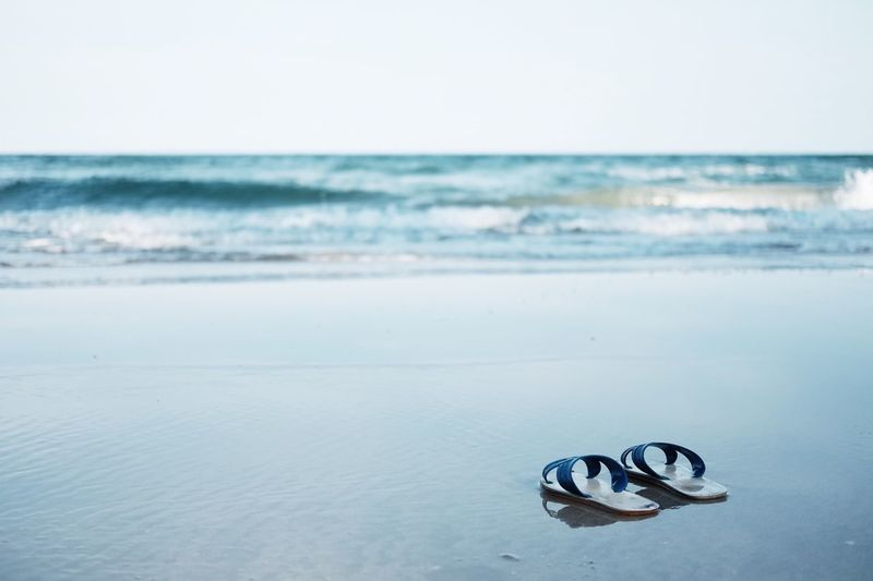Flip-Flops On Shore Against Clear Sky