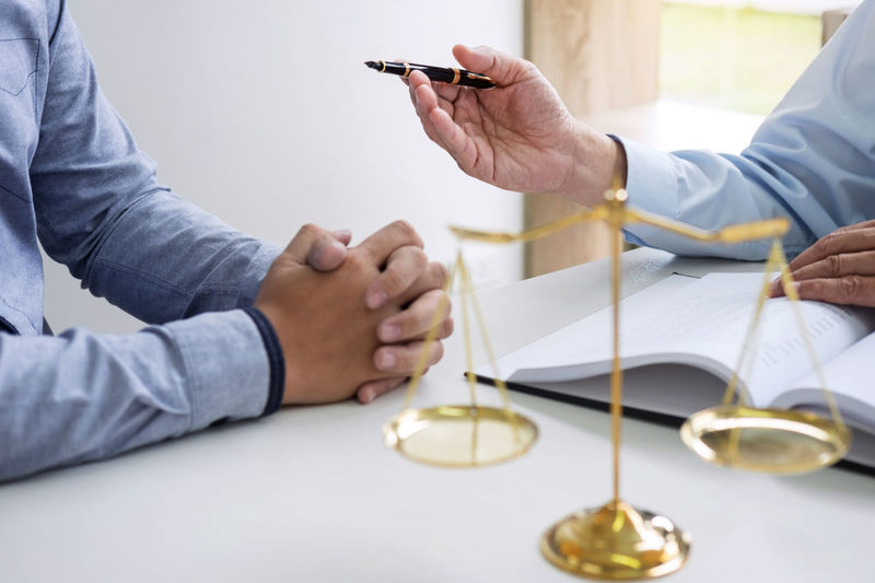 Midsection Of Lawyer Discussing With Client At Desk In Office