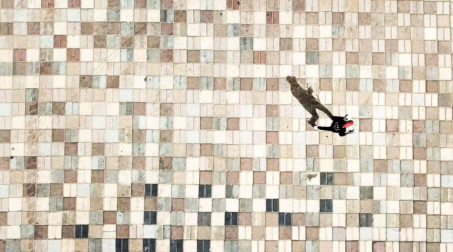 High Angle View Of Man Walking On Tiled Floor During Sunny Day