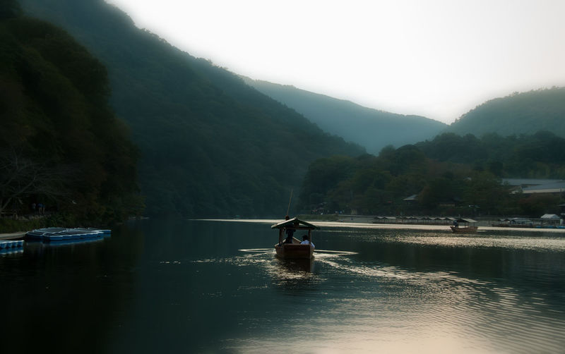 Boat sailing in river against mountains