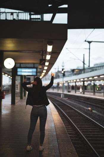 Rear view of young woman holding string light standing at railroad station platform