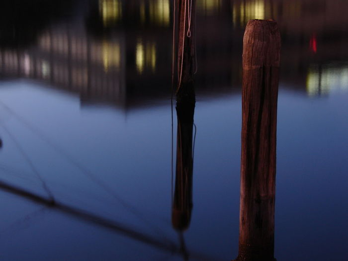 Close-up of wooden poles in water