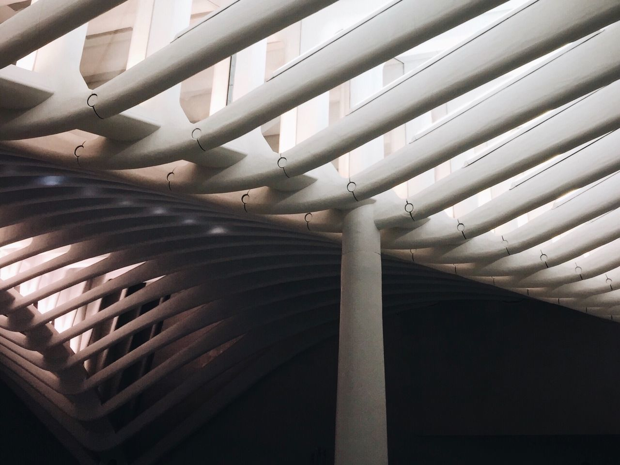 indoors, no people, pattern, ceiling, architecture, white color, built structure, metal, day, close-up, architectural column, low angle view, technology, repetition, roof, building, lighting equipment, pipe - tube, wood - material, roof beam