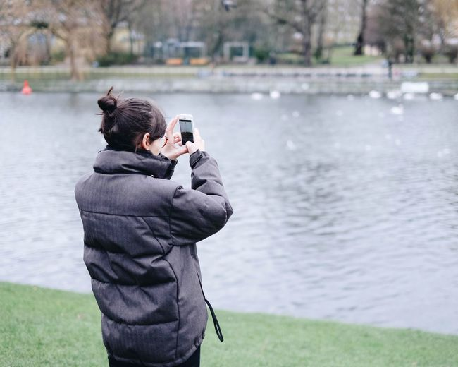 Rear View Of Young Woman Photographing While Standing By Lake At Park