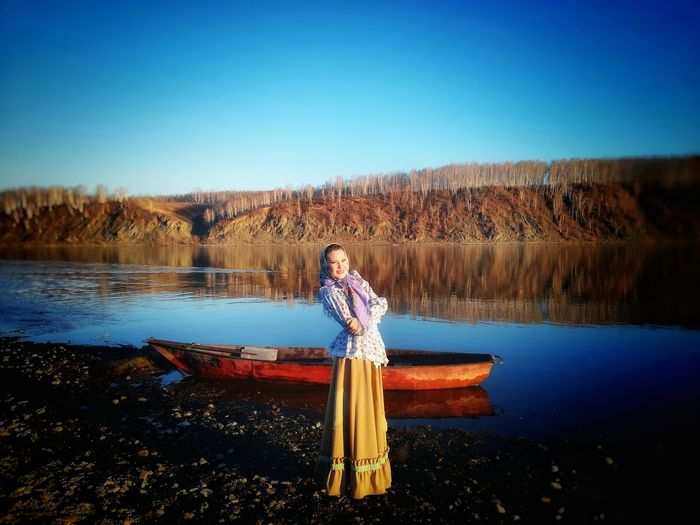 Portrait of woman standing by lake against clear blue sky