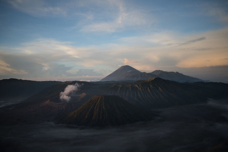 View of volcanic landscape against cloudy sky bromo