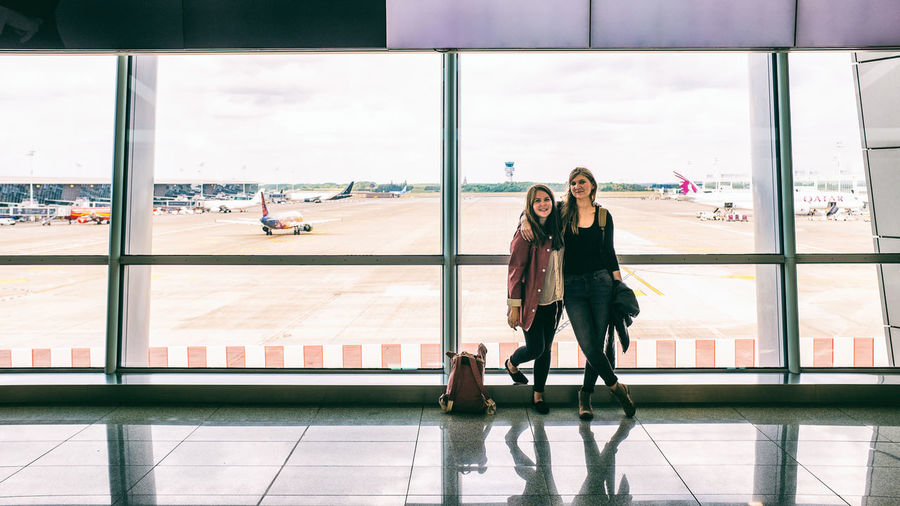 Runway Adult Airplane Airport Airport Runway Day Friendship Full Length Indoors  Lifestyles People Real People Sky Transportation Travel Two People Window Women Young Adult Young Women