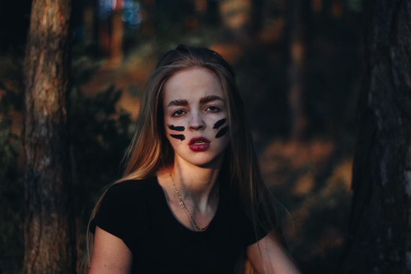Portrait of woman with face paint in forest