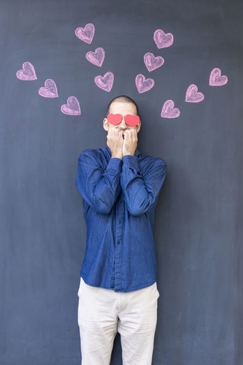 Single adult white man with heart shaped eyes wearing a blue shirt and standing in front of a blackboard with painted hearts. Concept of crazy love Emotions Love Romance Romantic Valentine Valentine's Day  Adult Blackboard  Blue Casual Clothing Crazy Front View Heart Heart Shape Humor Love ♥ Lovely One Man Only One Person Pink Color Real People Standing Valentine's Day - Holiday Valentinesday White Color