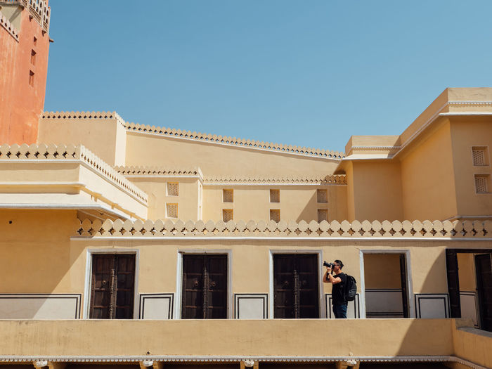 Man photographing while standing in balcony against clear sky