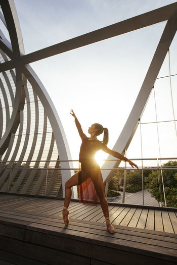 Ballerina dancing on bridge against clear sky