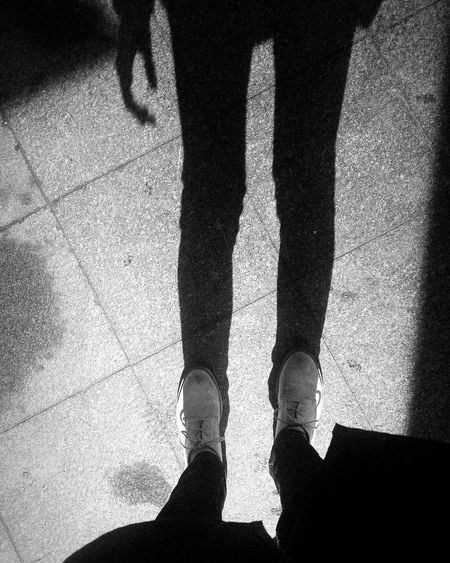 Low section of man standing on shadow