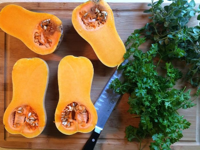 Directly Above View Of Fresh Halved Pumpkins With Coriander And Knife On Cutting Board