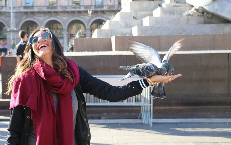 Cheerful woman feeding pigeons in city