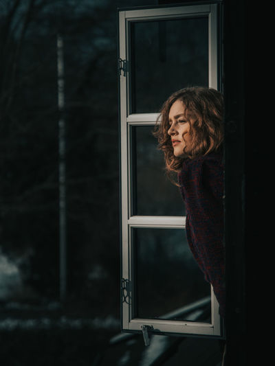 Woman looking through window at night