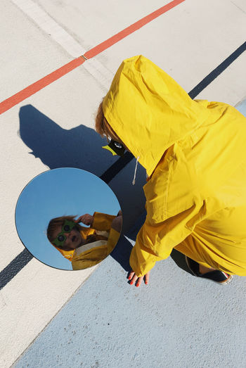 High Angle View Leisure Activity Lifestyles Sunlight Yellow Day Real People Shadow Reflection Raincoat Mirror Mirror Reflection Round Round Shape Glasses Fun Having Fun Girl Young Adult Young Women Colors Colorful Girls One Person Dazed