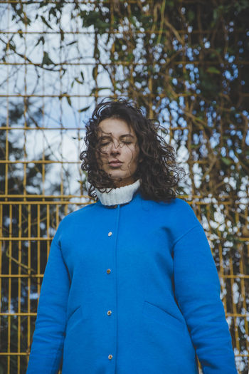 Portrait of Helen. International Women's Day 2019 Focus On Foreground One Person Waist Up Young Adult Real People Woman Standing Casual Clothing Blue Clothing Outdoors Hairstyle Fence Coat Window Windy Face Moody Lifestyles