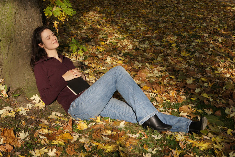 Smiling woman with book reclining on tree at park during autumn