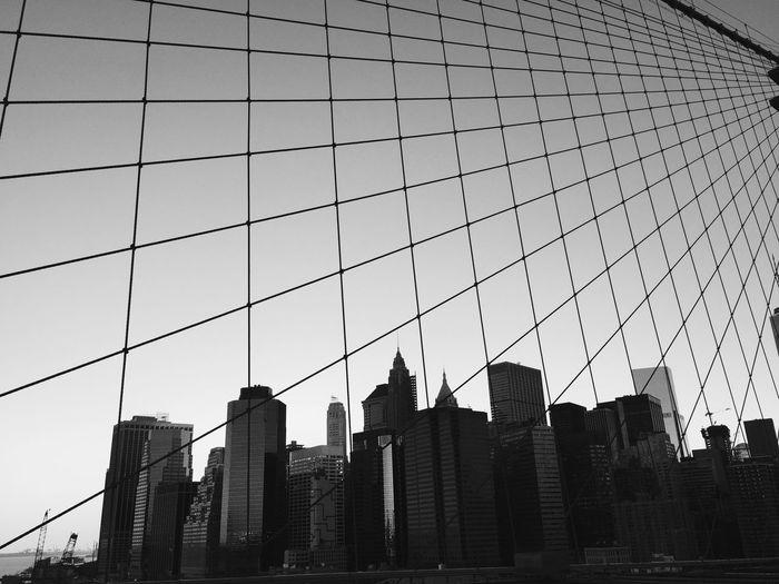 Modern Buildings Against Sky In City Seen Through Brooklyn Bridge