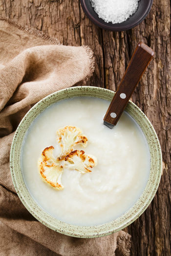 Fresh homemade cream of cauliflower soup garnished with roasted cauliflower floret slices, served in bowl with spoon, photographed overhead on rustic wood (Selective Focus, Focus on the soup) Food And Drink Food Freshness Bowl Ready-to-eat Healthy Eating Healthy Soup Appetizer Cauliflower Cruciferous Vegetable Cole Vegetarian Cream Creamy Cream Soup Meal Dish Cooked Homemade Fresh Natural Blended Puree