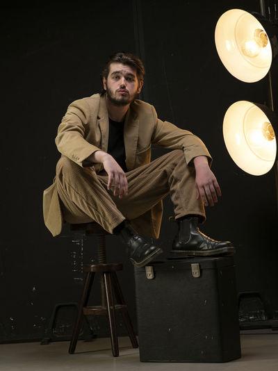 Male model sitting on chair looking foward