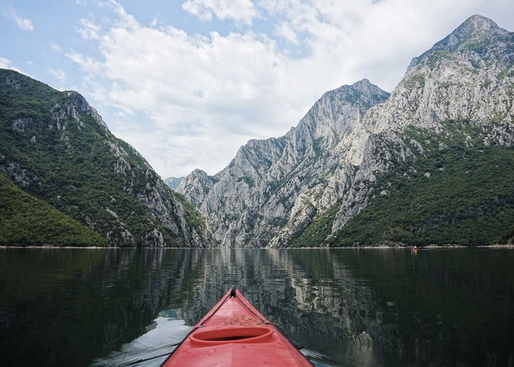 Scenic view of lake, kayak and mountains against sky