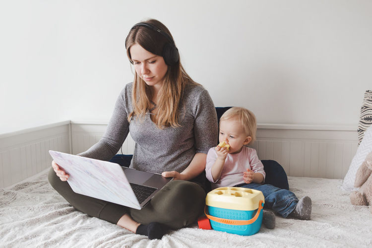 Mother using laptop while sitting with baby girl on bed at home