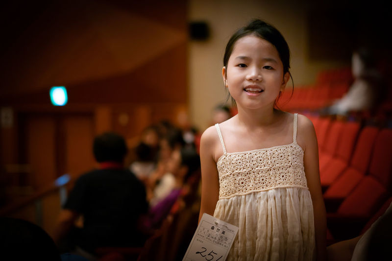 Portrait of smiling girl standing in stage theater