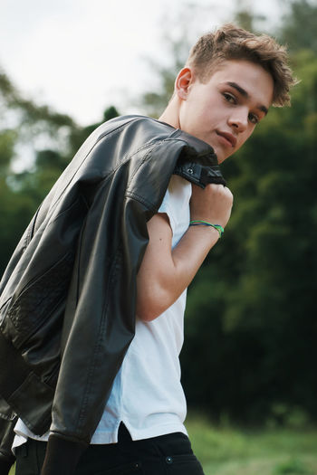 Side View Portrait Of Teenage Boy With Black Leather Jacket Standing At Park