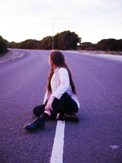 Young woman sitting on road against sky at sunset