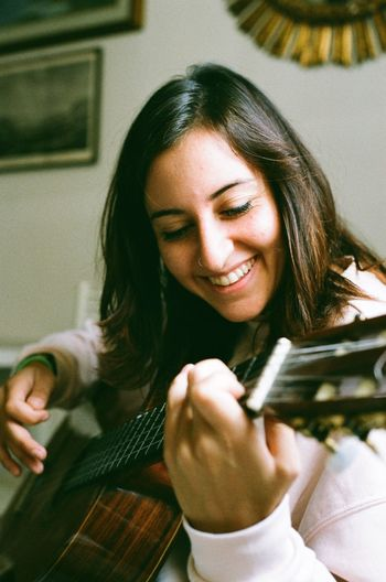 Smiling young woman playing guitar while sitting at home