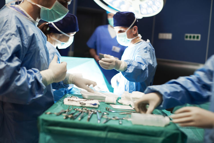 Busy surgeons during difficult operation Surgery Medical Equipment Pass Surgeon Operating Room Assistance Surgical Glove Human Hand Sterile Teamwork Operation Hospital Doctor  Specialist Clinic Dark Illuminated Tool Surgical Equipment Operating Table Table Surgical Medical Care Group Of People Professional Occupation Medical Occupation Uniform Work Busy Nurse Idea Apron Cooperation Service Occupation Man WorkWear