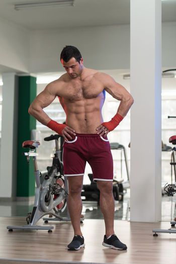 Full length of shirtless man standing against wall