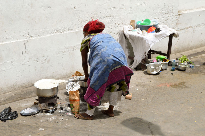 Rear view of poor woman cooking on stove by wall on street