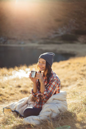 Young woman drinking coffee while sitting on land