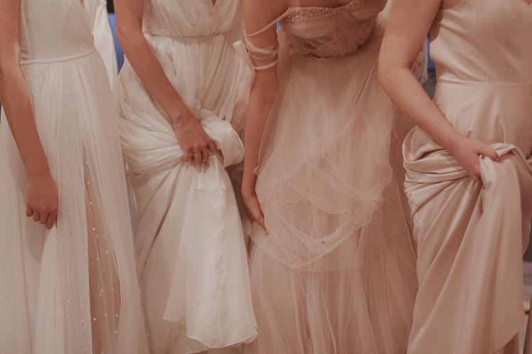Cropped figure of women holding the hem of a long dress. wedding fashion