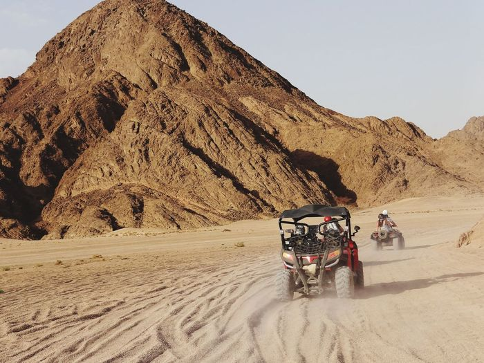 Rear View Of Friends Riding Off-Road Vehicle In Desert Against Mountains